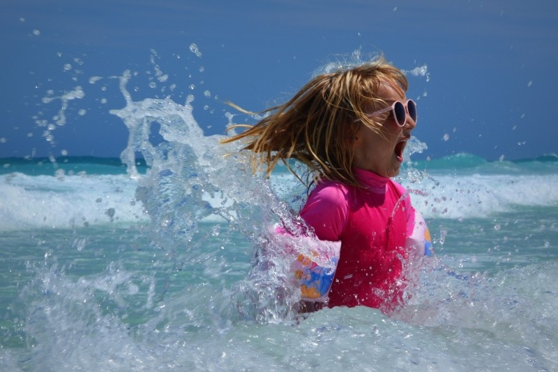 child-girl-sea-waves-fun-ocean-wetsuit